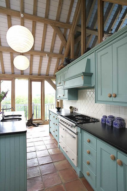 Barn conversion ... dont know wtf that is in front of the windows (looks like a dog gone bundy up or licking inself!! hahaa) But I do really love the blue cabinets! :)