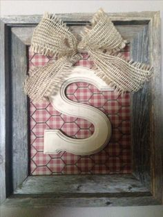 Monogram primitive wall decoration. Barnwood frame, glass removed. Gingham scrapbook paper, rusty chicken wire, and then a wood craft-store letter, sanded, painted white, then wood-stained. Screwed letter to back of frame, which also holds chicken wire and scrapbook paper to the back of the frame. Tied a big burlap bow through the chicken wire, put the whole thing back in the frame, and voilà!
