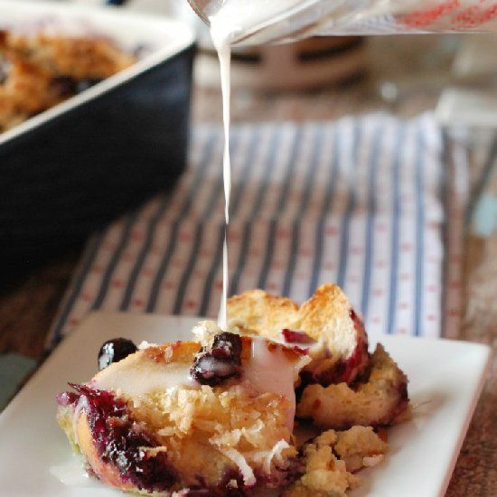 A simple baked, overnight french toast topped with coconut and plume, fresh blueberries.