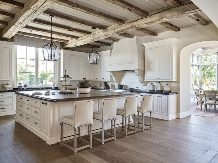 summer kitchen with wooden flooring, wooden beam ceiling, arch walls, white kitchen islands with brown top, white counter with black top, white big cooker hood  of Welcoming Summer with Cooking Al Fresco