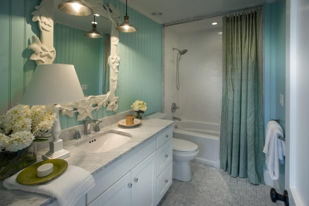 Bright floor-to-ceiling beadboard and a decorative mirror lend whimsical qualities to this kid-friendly bath. From the experts at HGTV.com.