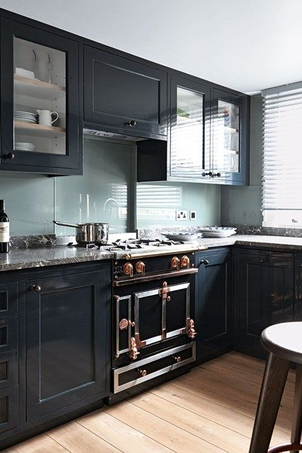 Explore our kitchen design ideas on HOUSE by House & Garden, including this kitchen with black units and light oak flooring.
