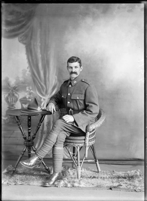 Studio portrait of unidentified soldier with moustache in uniform wearing putties, sitting in cane chair at table with hat, Christchurch 1914ca