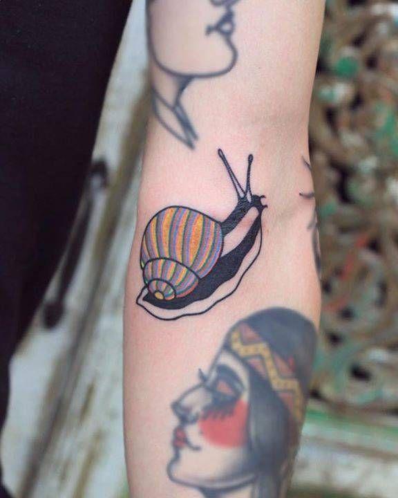 Snail tattoo on the left arm.