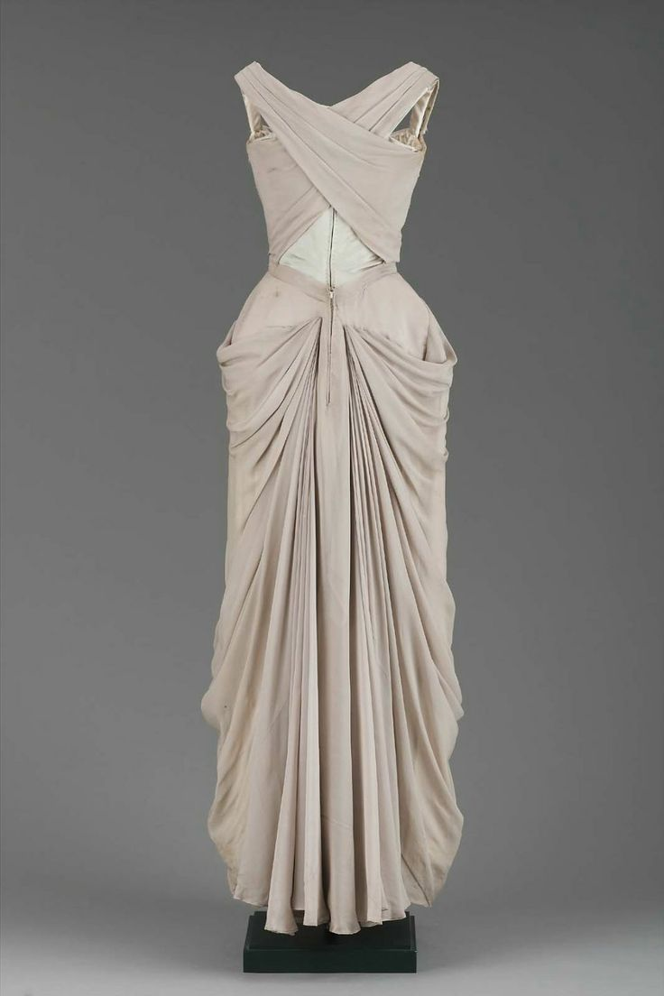 Charles James Evening dress of gray pearl silk chiffon over silk satin. Bodice has wide straps and draped chiffon. Skirt also has draped chiffon swagged around hips and brought to back in seam. (back view)