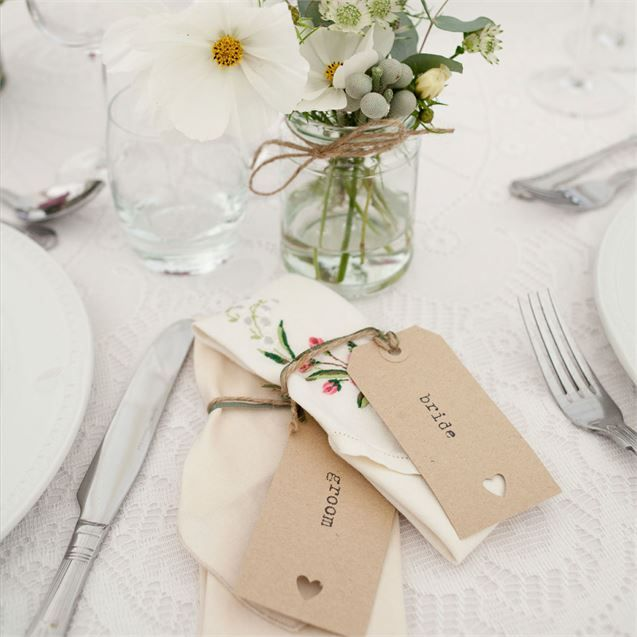 Each table at Jo and Neil's gorgeous garden reception was named after a place they loved. Table names included Constantine, Haldon, Bovey, Polzeath, Watergate, and Croyde. Each guests' place was marked by a vintage style luggage tag, printed with their names and decorated with a heart cut out. Jo got these pretty place cards from eBay.The couple hired Dartmoor Kitchen, who took care of the catering at fashion designer Savannah Miller's wedding, to cater for their wedding reception, and opted…