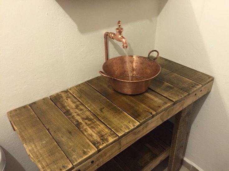 Lavabo hecho con un cazo de latón, tubería de cobre y llave de bronce con terminación en latón. Todo montado sobre madera utilizada para cimbra, sellada con poliuretano a base de agua.