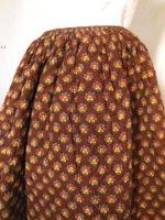 Belle jupe piquée ou cotillon matelassé en indienne à grand semis datant d'avant 1850. Piquage en petits losanges serrés, cette jupe est très souple et légère car on note peu de ouate de coton entre les deux couches de coton. L'Indienne de dessus est à grands semis stylisés de couleur bleu, rouge, jaune et vert sur fond marron/aubergine.
