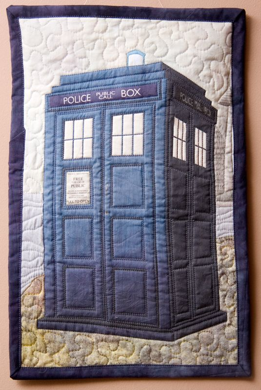 The technique I settled on was to choose the fabrics for the ground, water, and sky, scan them in to the computer, and piece them there for the background.  Then I created the tardis graphic and the building, then printed it on fabric with Bubble Jet Set.