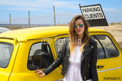 Young Hippie girl standing next to an old vintage, retro car