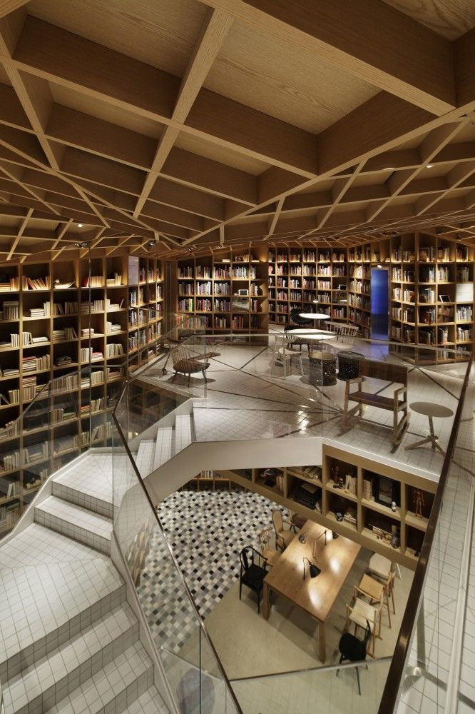 "Hyundai Card Travel Library, Seoul, South Korea. It is a ""travel library"" and café that have been designed with a theme of travel. The concept of the design is a ""stock of curiosity."" The act of visiting this place is interpreted as a form of travel, and the space exhibits a thick accumulation of information, experience, and objects, including a bookcase that covers the entire wall from floor to ceiling."
