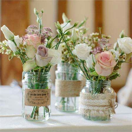 Wedding flower floral arrangements in mason jars with burlap and lace embellishments