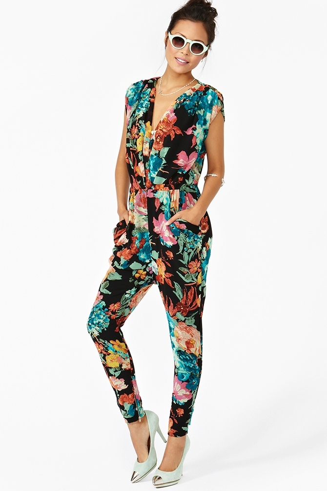 Ah-mazing black chiffon jumpsuit featuring a plunging wrap top and bold floral print. Hip pockets, stretch panel at waist. Ankle zip closures, fully lined. Looks perfect with bright lips and platform pumps! By Gypsy Junkies.