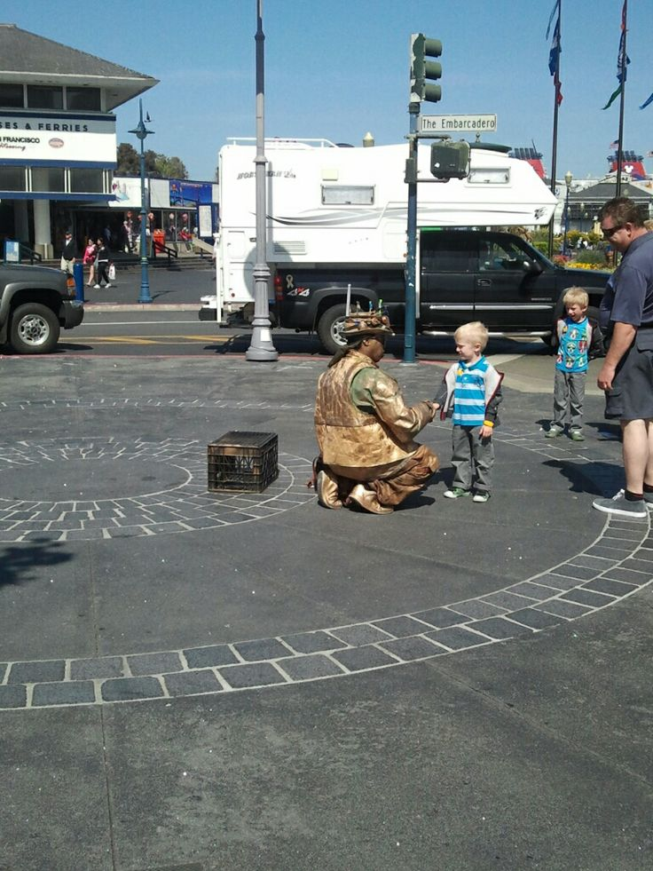 The performer is kneeling his knees to meet the eyes of the child. :)