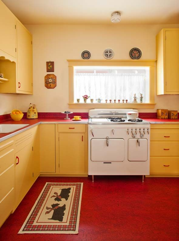 Great 1940's retro kitchen redesign. Kitchen accents include vintage working accessories: a hammered aluminum platter, a beehive cookie jar, a tin cake plate, and hand-painted wood canisters. Love the Marmoleum matching red on the floor and countertops!