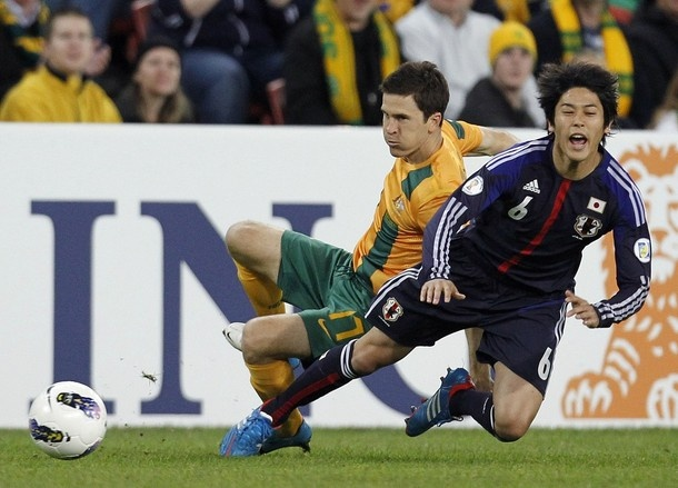 20120612 Australia's Matt McKay (L) fights for the ball with Japan's Atsuto Uchida during their 2014 World Cup qualifying soccer match in Brisbane June 12, 2012.