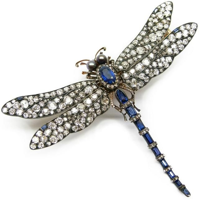 Antique sapphire, pearl and diamond tremblant dragonfly brooch, c.1895, with pave set diamond wings, an oval cut sapphire and rose diamond cluster thorax, the tail formed by a tapering row of sapphires with rose diamond set divisions, two grey-black pearls forming the eyes, diamonds to the legs and anteannae, open set in silver and gold.
