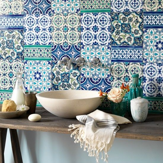 Create a feature wall with Moroccan-inspired ceramic tiles in various shades of blue. A stone vessel basin set on top of a reclaimed table adds a rustic touch