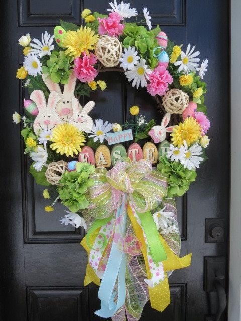 The focal point of this Easter/ spring door wreath is an wooden Easter Bunny Family trio and a wooden Happy Easter sign. The base is an 18 grapevine wreath to which I have added silk florals including green hydrangeas and their foliage, yellow Gerber daisies, white daisies, mini yellow carnations and ranunculus. Foam Easter eggs are interspersed throughout the wreath. Natural fiber decorative ornaments can be seen amidst the foliage and florals. An XL bow was fashioned from pastel color...