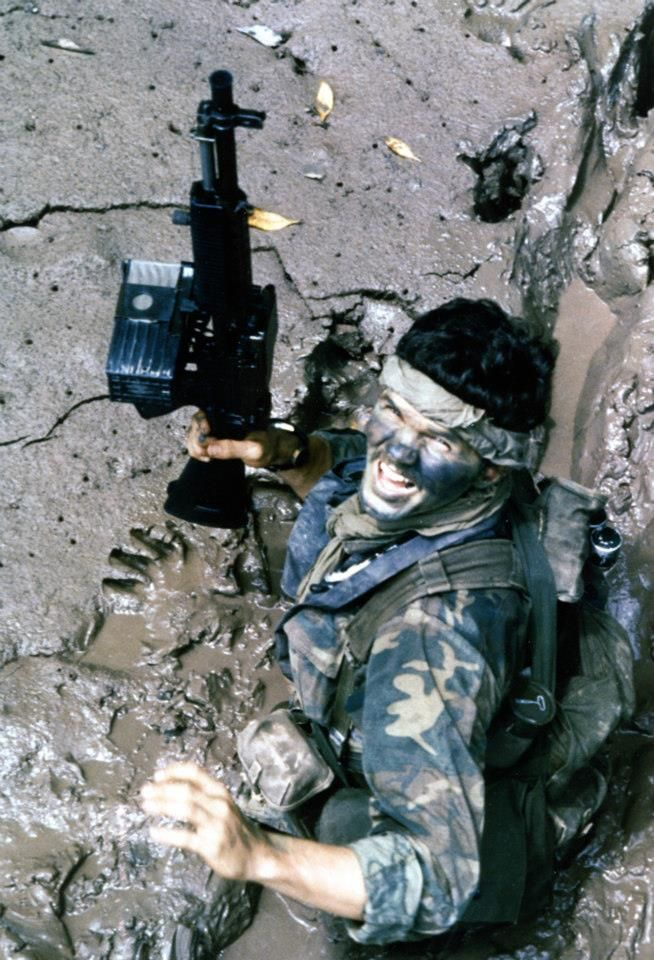 A Navy SEAL, carrying a Mk23 5.56mm Machine Gun (Stoner 63), moves through deep mud as he makes his way ashore from a boat, during a combat operation in South Vietnam in 1970. (U.S. Navy photograph by PHC A. Hill)