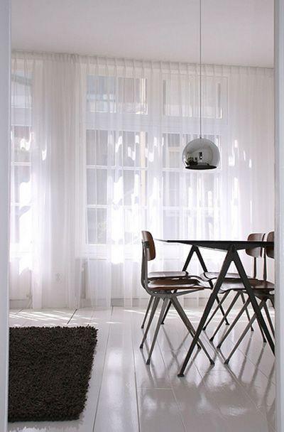 Lichte gordijnen maken een minimalistische kamer zachter en filteren licht, waardor een rustige sfeer ontstaat.