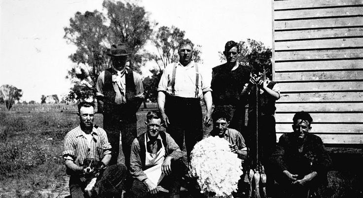 A shearing team on 'Glencoe' station. One man holds a dog, another holds fleece while the rousteabout holds a bundle of brooms. Mockinya, Victoria, 1936