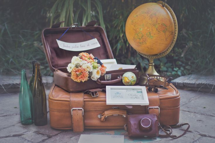 Travel inspired colorful wedding decorations. Vintage suitcases, globe decor and beautiful flowers