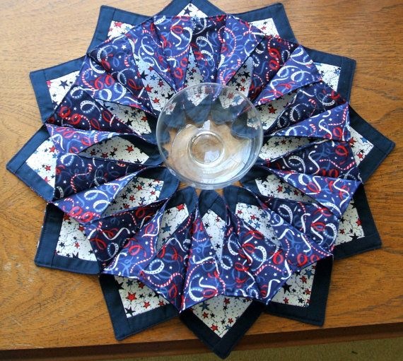 This brightly colored patriotic centerpiece measures 18 across its outside points with a 3 center space. One consists of exploding red, white and blue fireworks on a navy background fabric and a white fabric bordering a square of red. It would be spectacular supporting a footed plate. Or it can be used with a candle in the center or simply a pretty bowl of treats. It can also be used on a picnic table with cutlery placed in each of the twelve petals. Another has stars bordered by the dark…