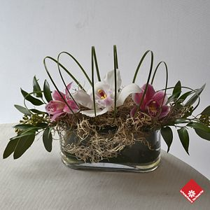 A trio of cymbidium orchids arranged in an oval glass vase