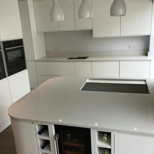 This all white kitchen features glossy style cabinetry and the Bianco De Lusso quartz on the worktops. It is a very practical kitchen and features black appliances to mix up the colour style as well as the dark flooring.