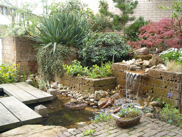 Deze kleine patiotuin heeft een oosterse brug door de vijver en een beekje met overloop door de plantenbakken van tufsteen. Vanuit het huis heb je jaarrond een levend schilderij om je heen. www.houdijkstijltuinen.nl