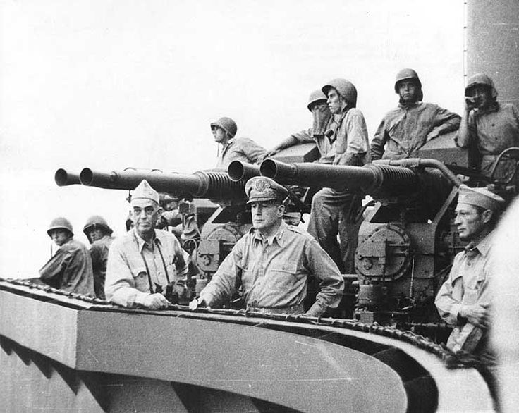 Vice Admiral Thomas Kinkaid, General Douglas MacArthur, and Colonel Lloyd Labrbas aboard cruiser Phoenix during bombardment of Los Negros Island, 28 Feb 1944; note 40-mm gun mount in background.