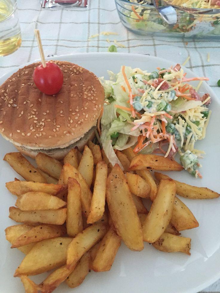 Hamburger broodjes met tartaar hamburger met rood uitje, bieslook en hamburgerkruiden. Verse frietjes van kruimige aardappelen en een 7 lagen salade van: Ijsbergsla, wortel rauwkost, lente ui, diepvries erwten, laagje dressing van yoghurt, mayonaise dille zout en peper, oude geraspte kaas en uitgebakken spekjes.
