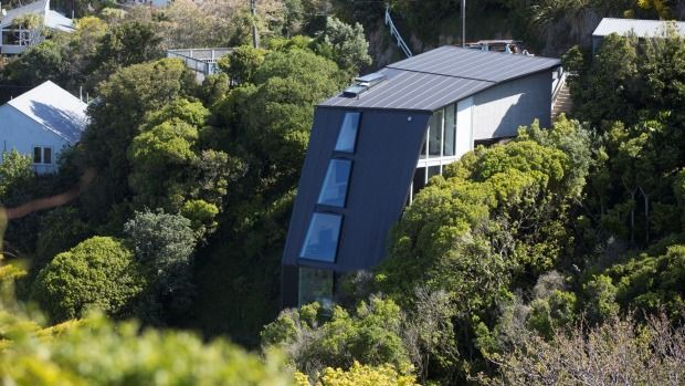 Steel cables and rock anchors secure this multi-level Wellington house to the cliff, so it appears to float above the bush.