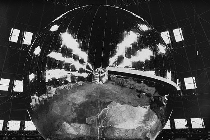 A TEST INFLATION OF THE ECHO 1 COMMUNICATIONS SATELLITE IN 1957. NOTE THE TINY HUMANS IN THE FRAME