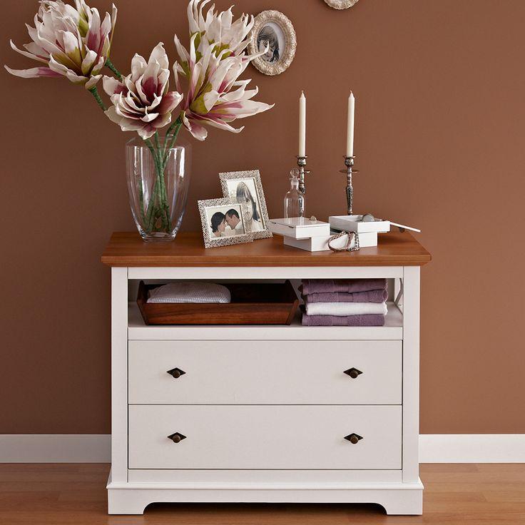 Comoda Elisabeth. Stilul londonez este vizibil în geometria mobilierului, în regularitatea și repetarea liniilor, formând un ritm optic. Albul mat oferă senzația de liniște și puritate, în timp ce blatul de culoarea mierii, încălzește și face plăcută ambianța.