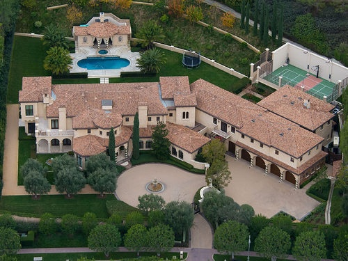This Los Angeles home, owned by slugger Barry Bonds, has stucco walls, Spanish tile roof, arched openings, covered walk ways, tower pieces, a pool, pool house and tennis court.