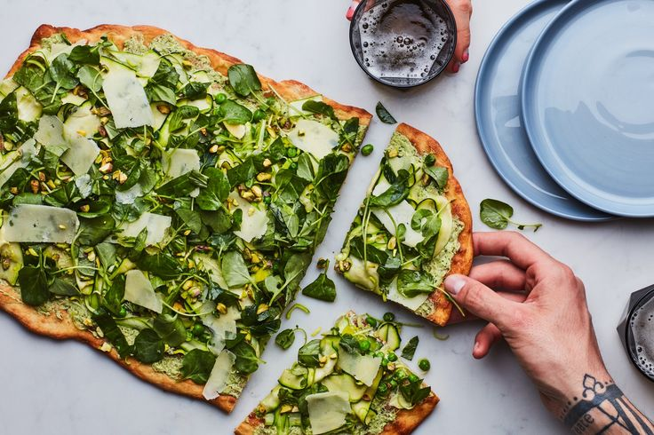 This fresh take on white pizza has a base of pesto and white cheeses topped with a veritable salad of all our favorite green vegetables. Peas and crispy, thin-shaved asparagus, zucchini, and leeks are topped with watercress, basil, and pecorino curls for a satisfying slice that just happens to be vegetarian.