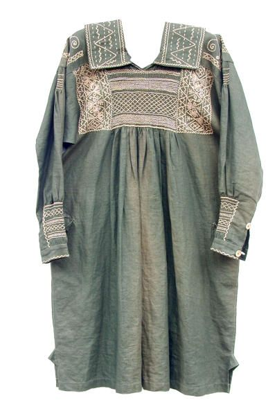 Made in Danbury, Essex c.1900. This is a reversible smock made from green linen and cream thread. It is hand sewn. There is smocking on the chest at front and back, and on the sleeves at the top and above the cuff. There is embroidery on the chest at front and back, and on the collar, yoke, sleeves and cuffs. Unworn. Museum of Rural Life