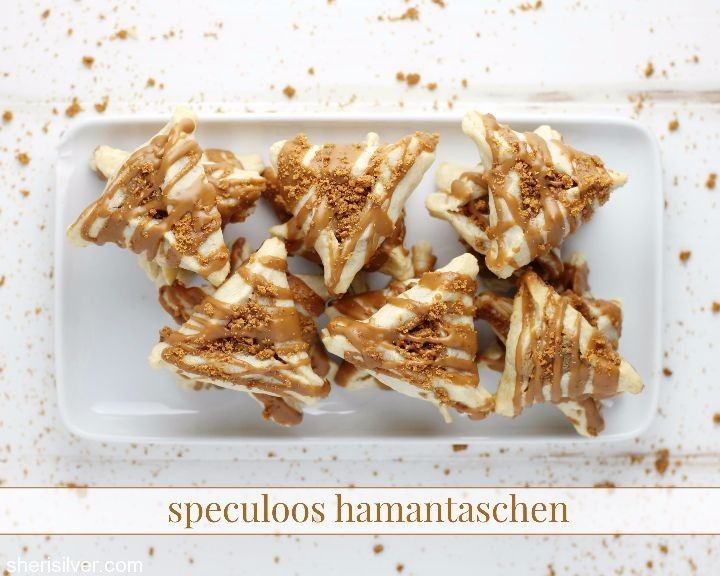 Love cookie butter - a.k.a., speculoos? Then you will LOVE these irresistable hamantaschen, filled with cookie butter dip, drizzled with melted cookie butter and sprinkled with crumbled Biscoff cookies!