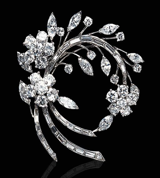 A DIAMOND AND PLATINUM BROOCH   Designed as a circular and baguette-cut diamond floral spray, accented by marquise-cut diamond leaves, mounted in platinum