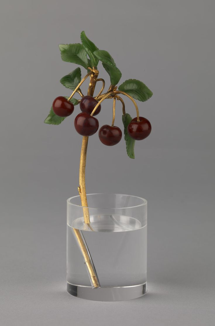 A FABERGÉ WILD CHERRY STUDY, WORKMASTER HENRIK WIGSTRÖM, ST PETERSBURG, 1908-1917 A realistically chased gold stem with delicately carved nephrite leaves and red agate cherry fruits resting in a cylindrical rock crystal pot. Flower studies are among the most desirable and unforgettable objects of fantasy made by Fabergé. Only a small number of wild cherry studies are known to exist, most notably, one in the British Royal collection which was purchased by Queen Alexandra.
