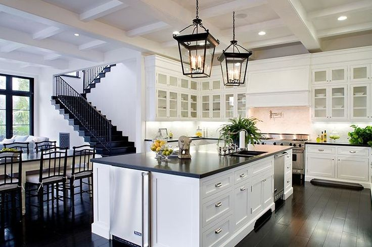 Eat in kitchen in a Spanish revival home with two lantern lights, white cabinets with glass fronts, coffered ceiling, and a white island with black countertops