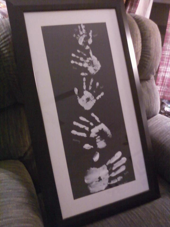 Family Tree Hand Print. Using black poster board, white paint for the hand prints and a white marker to write who is who and the month and year it was made. Placed in a black frame with a white mat. I'm so doing this! (but in brown colors)