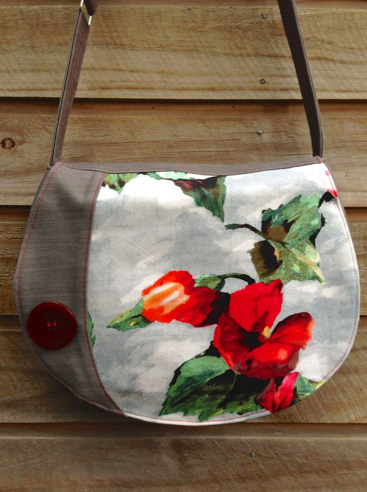 large round satchel in beautiful big bloom fabric with red button and magnetic close. <3