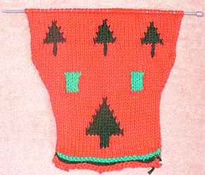 Red dog Christmas sweater being knitted with green tree and gift box designs.