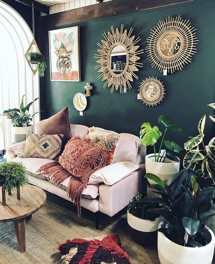 Deep green emerald walls with greenery and blush pinks and mauve with gold accent mirrors