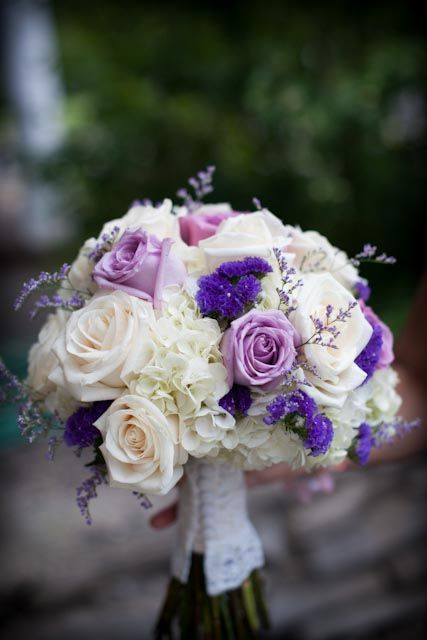 Beautiful purple, lavender, and white wedding bouquet. Designed with white hydrangeas, ivory and lavender roses, purple statice, and lavender limonium. Wrapping the handle in the sleeve from our bride's mom's dress makes it extra special. By Backyard Garden Florist.