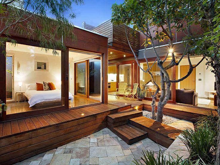 UNA CASA EN MELBOURNE   Decorar tu casa es facilisimo.com Casa unida por una terraza cubierta en madera los dos cubos que la comprenden.Los árboles estratégicamente puestos y las vistas desde todas las partes de la casa al jardín la hacen deliciosa.