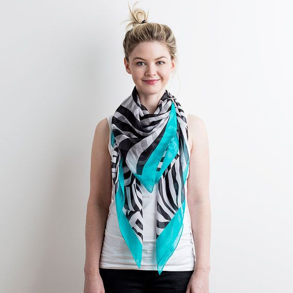 Now now, dont squeal, but have you had a really good look at this design? Have you found our hidden little friend camouflaged in there? We know, how awesome is he! This beautiful silk scarf has been digitally printed in our zebra black and white print, but with a beautiful border of bright teal. It has hand rolled and stitched hems and even comes in a gift box!    Size: 127cm W x 127cm H  Details: 100% Silk Chiffon. Digitally Printed. Hand-Rolled Hem. Comes in a Gift Box